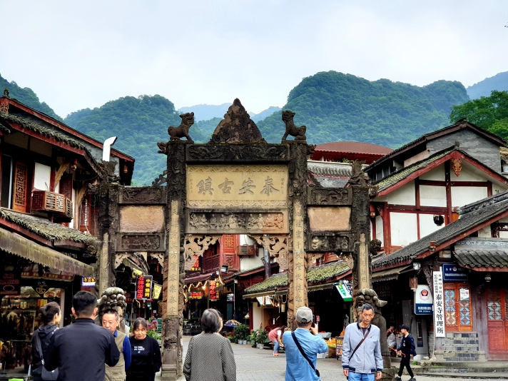 Tai'an Ancient Town entrance filled with people and a Qingchengmountain in the background